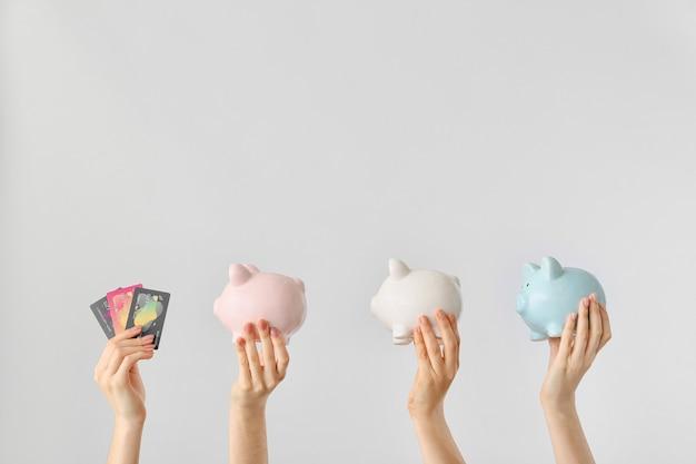 Mãos femininas com cartões de crédito e cofrinhos na luz.