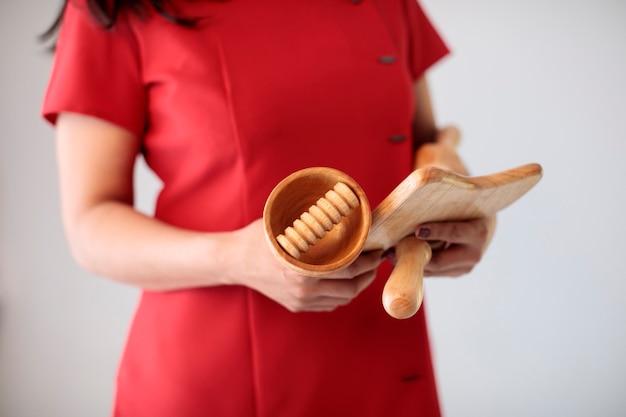 Mãos femininas com coleção de acessórios de madeira natural para massagem sem plástico e sem resíduos