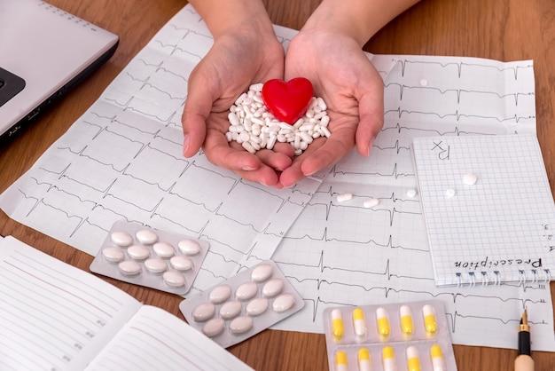 Mãos femininas com comprimidos brancos e coração vermelho