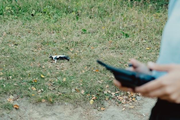 Mãos femininas com controles de um drone quadcopter ao ar livre no outono. a mulher começou a tocar o drone. mulher controlando drones voadores no parque