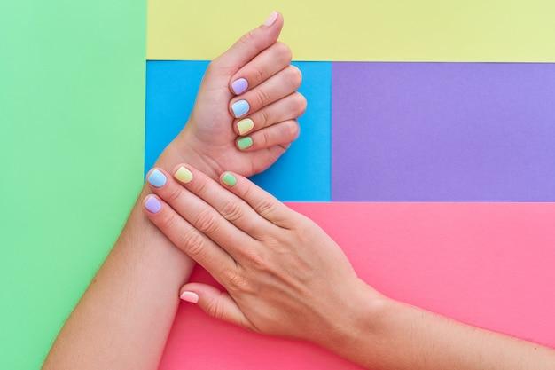 Mãos femininas com cores brilhantes em um fundo colorido