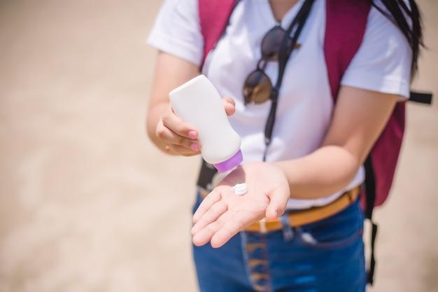 Mãos femininas com creme de proteção solar na praia. cuidados com a pele concep