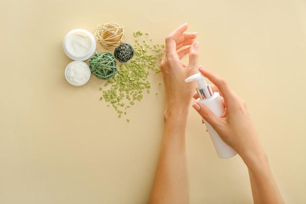 Mãos femininas com creme natural na parede colorida