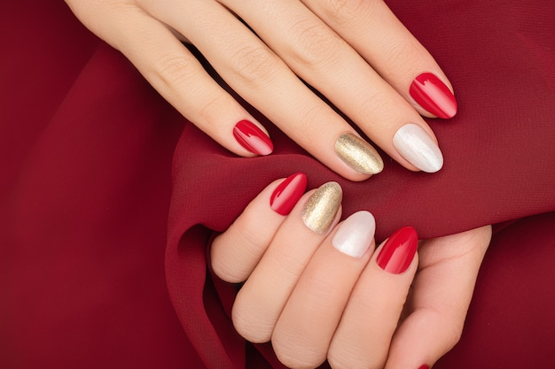 Mãos femininas com desenho de unhas vermelhas na superfície do tecido vermelho.