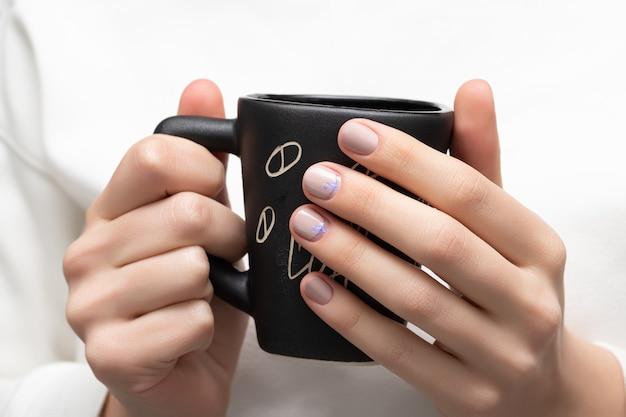 Mãos femininas com design bege unha segurando xícara preta.