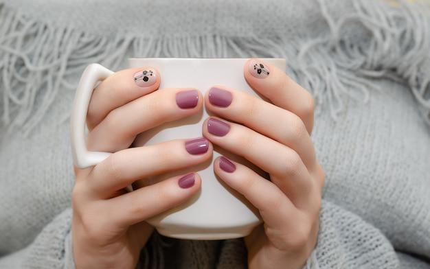 Mãos femininas com design de unha rosa escuro