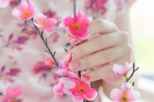 Mãos femininas com design de unha rosa.