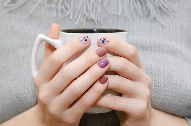 Mãos femininas com design de unha roxa segurando copo branco.