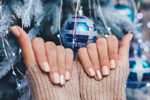 Mãos femininas com design de unhas de natal de ano novo. manicure com esmalte bege nu, um dedo bronze dourado brilhante