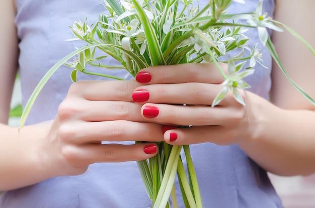 Mãos femininas com design de unhas rosa segurando o buquê de flores