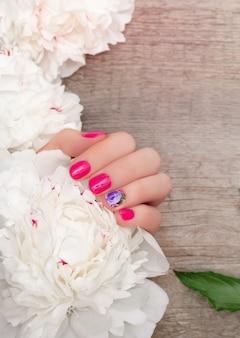 Mãos femininas com design de unhas rosa segurando peônias brancas