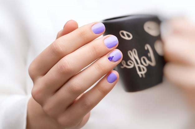 Mãos femininas com design de unhas roxas, segurando o copo preto.
