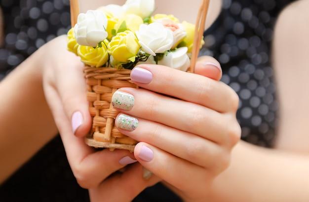 Mãos femininas com design de unhas roxo claro