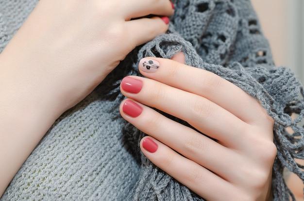 Mãos femininas com design de unhas vermelhas