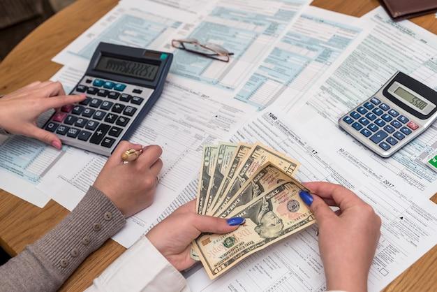 Mãos femininas com dólares e outros preenchendo formulário 1040