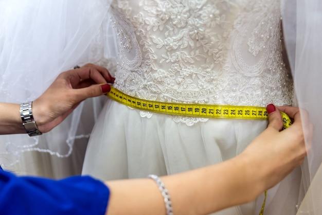Mãos femininas com fita métrica e vestido de noiva