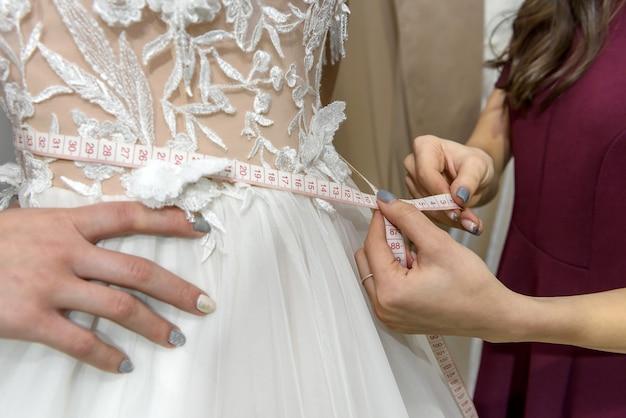 Mãos femininas com fita métrica na cintura do vestido de noiva