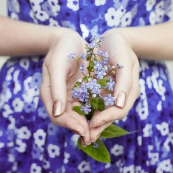 Mãos femininas com flores azuis
