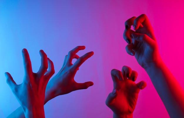 Mãos femininas com gestos assustadores. gradiente de luz neon azul-rosa