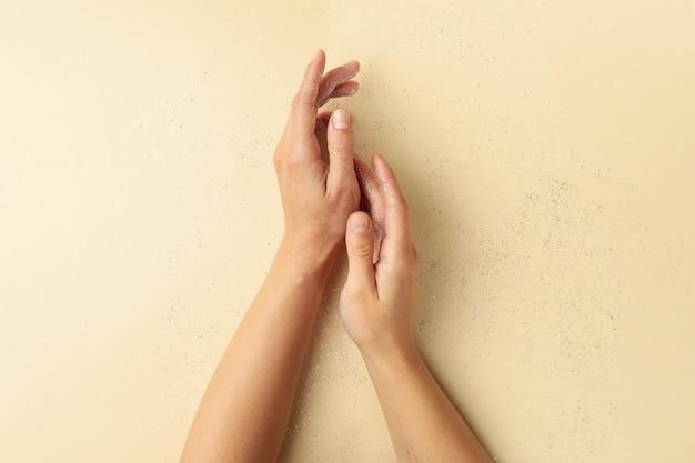 Mãos femininas com glitter em fundo bege