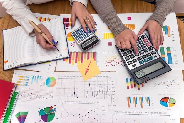Mãos femininas com gráficos de negócios e calculadoras