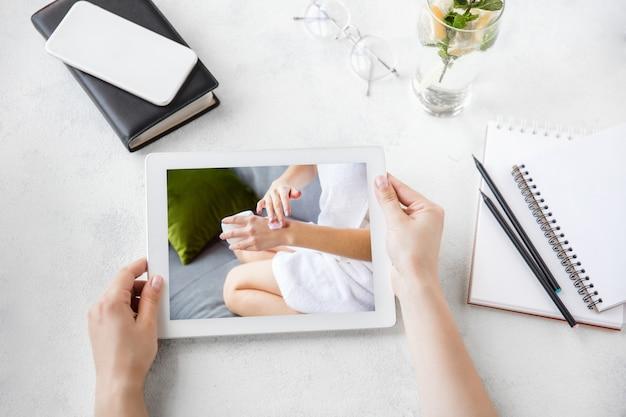 Mãos femininas com hidratante. tablet com promoção on-line na web de salão de beleza spa, cosméticos, beleza e autocuidado. copyspace para anúncio. vista superior do local de trabalho. dispositivos e gadgets, conceito de tecnologia.