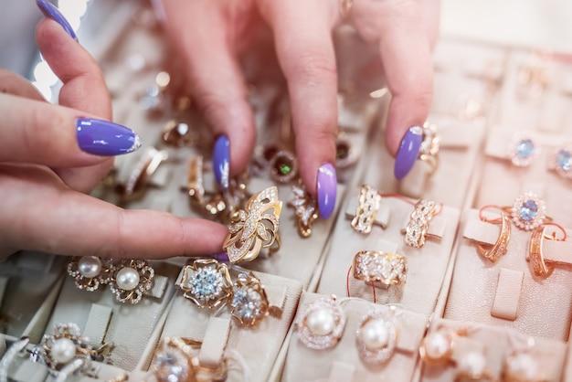 Mãos femininas com joias de ouro na loja fecham
