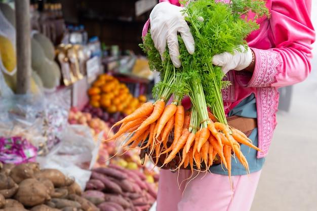 Mãos femininas com luvas brancas, segurando o monte de cenouras no mercado dos fazendeiros.