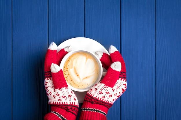 Mãos femininas com luvas de malha com padrão de ano novo segurar copo branco com cappuccino café quente na madeira azul
