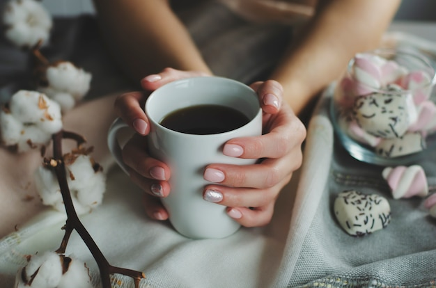 Mãos femininas com manicure colorido pastel segurando uma caneca branca com bebida