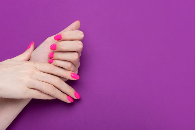 Mãos femininas com manicure de néon rosa sobre um fundo sólido roxo. lugar para texto