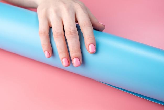 Mãos femininas com manicure de verão brilhante sobre um fundo azul e rosa