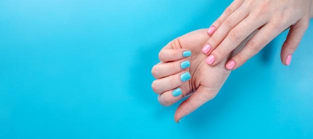 Mãos femininas com manicure de verão brilhante sobre um fundo azul