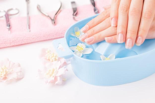 Mãos femininas com manicure e instrumentos na toalha