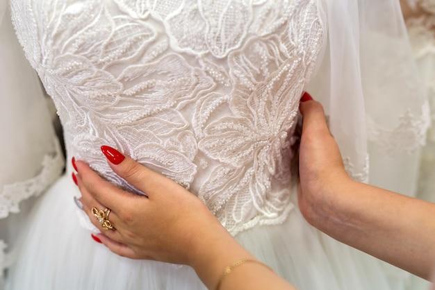 Mãos femininas com manicure e vestido de noiva, closeup