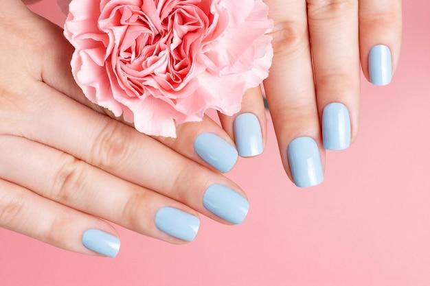 Mãos femininas com manicure em flor