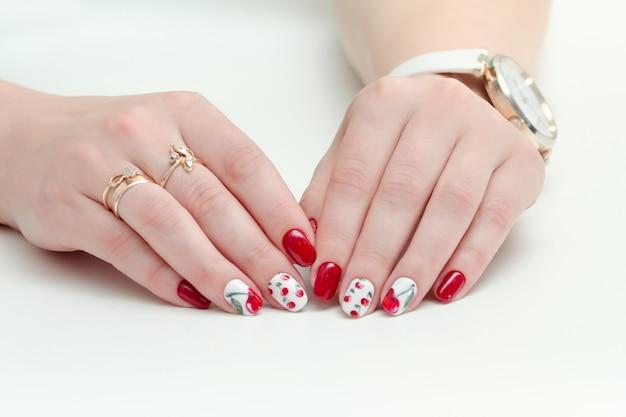 Mãos femininas com manicure, esmalte vermelho, desenho com cerejas. relógio de pulso. fundo branco.