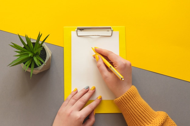 Mãos femininas com manicure fresca, escrevendo no papel. mesa de escritório, mesa, cores, amarelo e cinza, moda