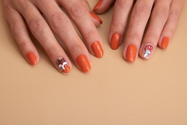 Mãos femininas com manicure laranja com um padrão sob um top brilhante. ideia criativa para mulher