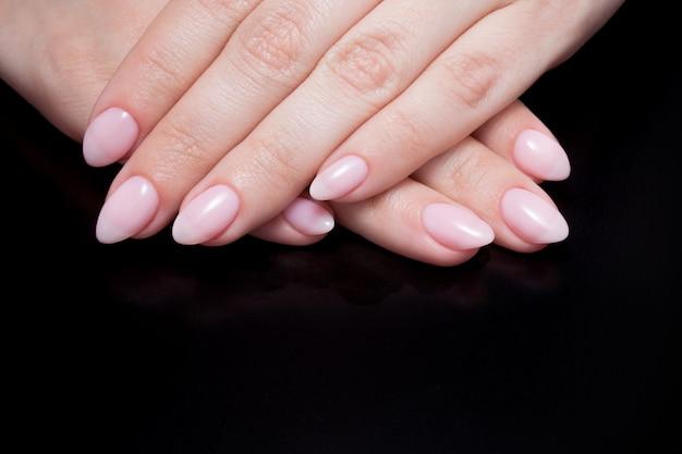 Mãos femininas com manicure nude perfeito.