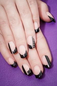 Mãos femininas com manicure preto