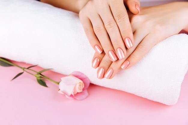 Mãos femininas com manicure rosa