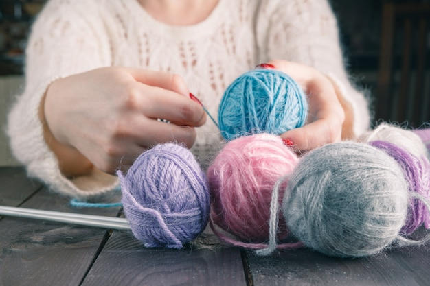 Mãos femininas com manicure roxo são raios de malha de metal de uma mesa de madeira.