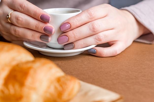 Mãos femininas com manicure segurando a xícara de café e comendo croissant. café da manhã em estilo francês