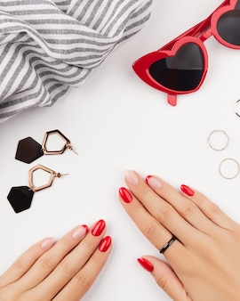 Mãos femininas com manicure vermelha e acessórios de moda nas tendências de design de manicure de parede branca