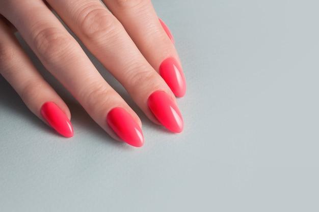 Mãos femininas com manicure vermelho perfeito. esmalte cor coral vermelho.