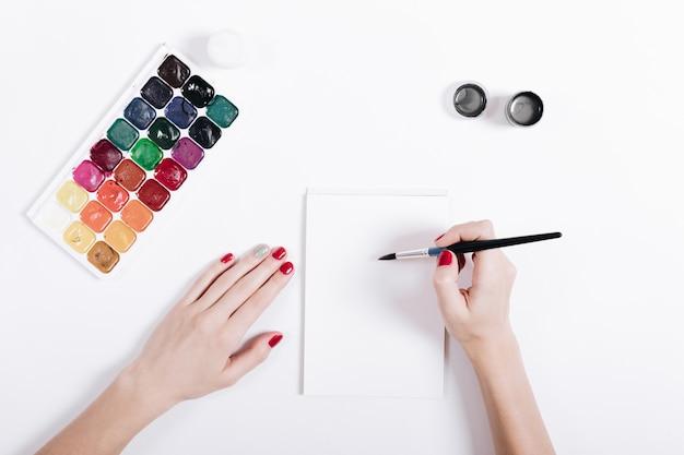 Mãos femininas com manicure vermelho pintaram aquarelas em um notebook