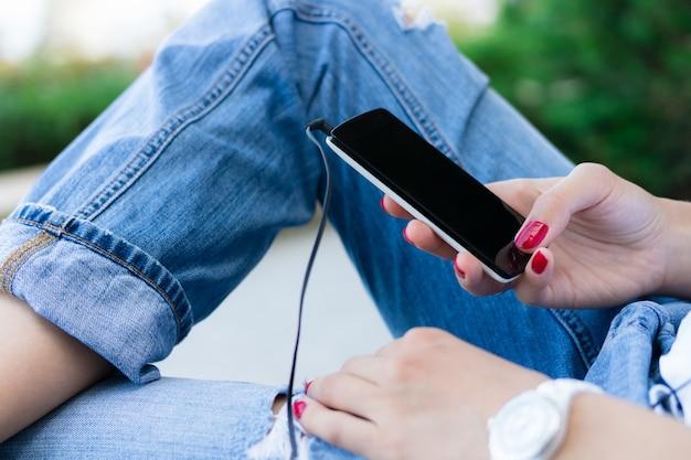 Mãos femininas com manicure vermelho segurando um telefone móvel com os fones de ouvido conectados