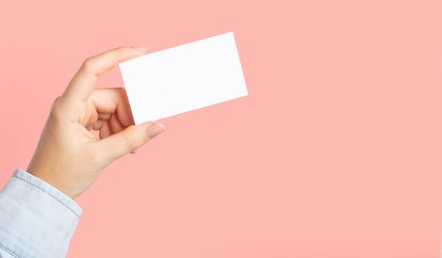 Mãos femininas com menu em branco, em corte, cartão de desconto, cartão de visita em fundo de beleza cor de rosa. modelo de design. modelo de maquete de marca