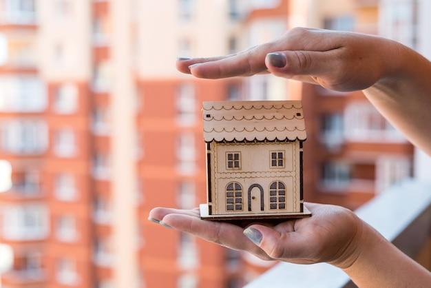 Mãos femininas com modelo de casa de madeira no fundo do canteiro de obras